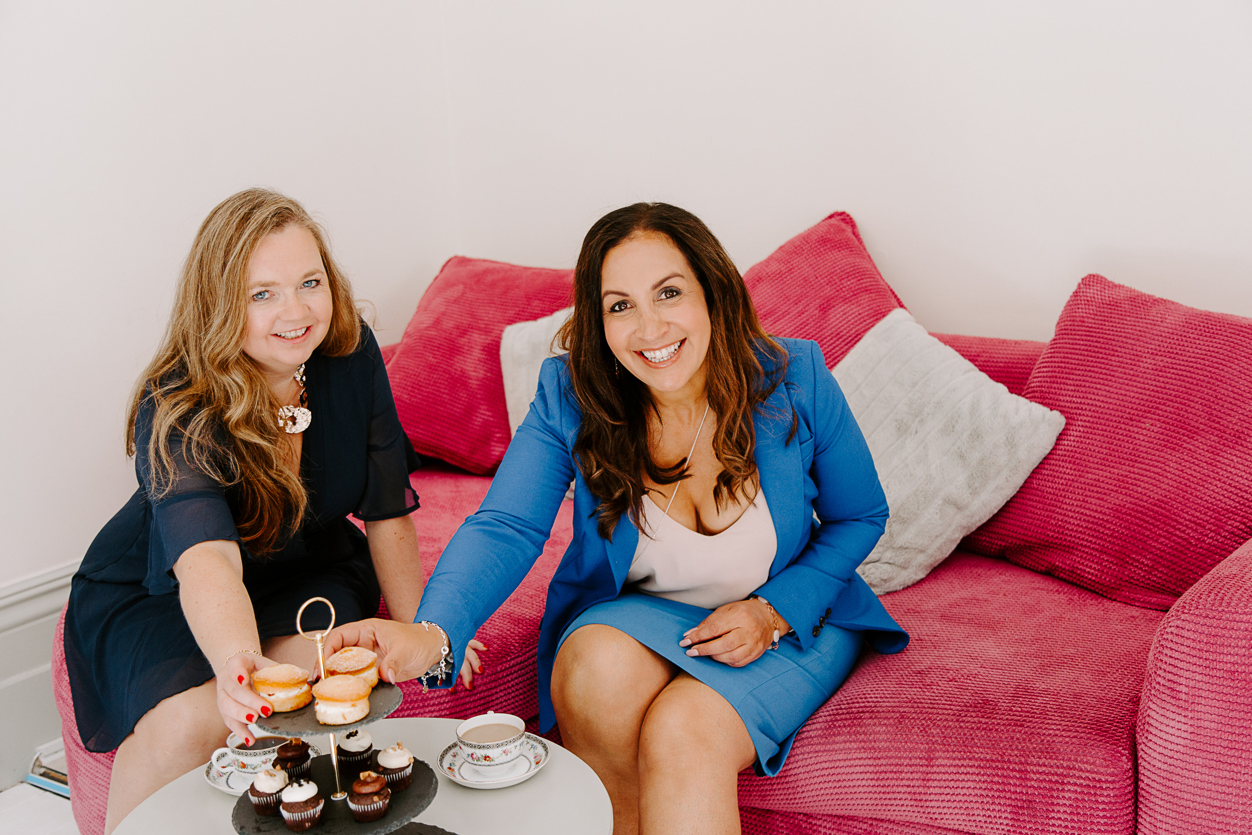 two woman sat on sofa